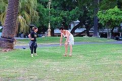 做平衡的女孩和人在公园 库存图片