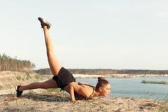 做平衡的瑜伽姿势和舒展在山的湖上流附近的一个可爱的少妇 库存图片