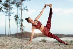 做平衡的瑜伽姿势和舒展在山的湖上流附近的一个可爱的少妇 免版税库存照片