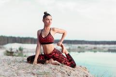 做平衡的瑜伽姿势和舒展在山的湖上流附近的一个可爱的少妇 图库摄影