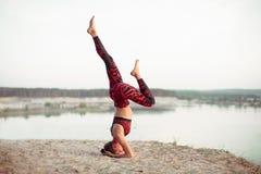 做平衡的瑜伽姿势和舒展在山的湖上流附近的一个可爱的少妇 免版税库存图片