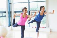 做平衡的瑜伽的适合的妇女在健身演播室摆在 免版税库存照片