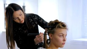 做年轻俏丽的妇女的专业美发师发型 免版税图库摄影