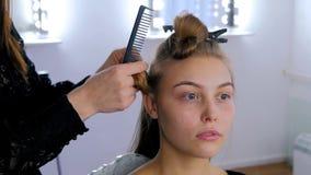 做年轻俏丽的妇女的专业美发师发型 库存照片