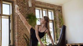 做年轻嬉戏的美女舒展在健身房的腿 做芭蕾锻炼的迷人的芭蕾舞女演员 芭蕾学校 影视素材