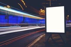 做广告假装与汽车的运动在背景的,在晚上删去路旁的社会信息委员会 免版税库存照片