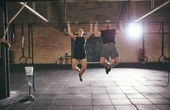 做引体向上的两位运动员前面射击  免版税库存照片