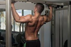 做引体向上的男性运动员 免版税图库摄影