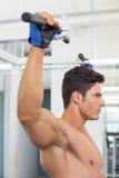 做引体向上的赤裸上身的男性身体建造者在健身房 免版税库存图片