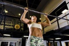 做引体向上锻炼的年轻坚强的妇女 免版税库存图片