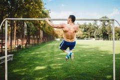 做引体向上,下巴的男性运动员在公园上升 解决和训练在公园的健身atheltic人 库存图片