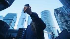 做录影的一个人在他的智能手机,当站立在企业大厦前面时 股票视频