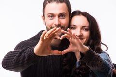做形状的微笑的秀丽女孩和她英俊的男朋友画象心脏由他们的手 库存照片