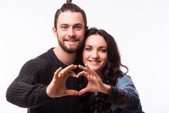 做形状的微笑的秀丽女孩和她英俊的男朋友画象心脏由他们的手 免版税库存图片