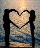 做形状的年轻夫妇与胳膊的心脏在海滩 免版税库存照片