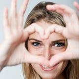 做心脏姿态的浪漫妇女 免版税库存照片