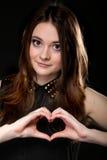 做心脏形状爱标志用她的手的女孩。 免版税库存图片