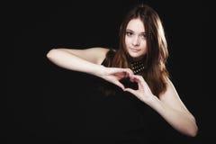 做心脏形状爱标志用手的青少年的女孩 免版税图库摄影