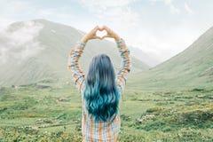 做心脏形状用她的在山的手的妇女 免版税库存照片