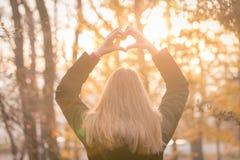 做心脏形状用她的手的女孩户外在日落 库存照片