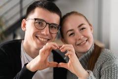 做心脏形状用手的夫妇特写镜头  免版税库存照片