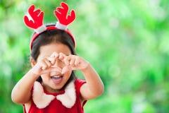 做心脏形状的圣诞节礼服的逗人喜爱的亚裔儿童女孩 免版税库存图片