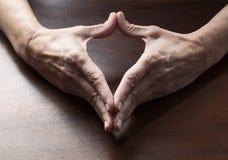 做心脏形状的成熟女性手 免版税库存图片