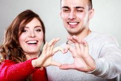 做心脏形状的年轻夫妇用人工 库存照片