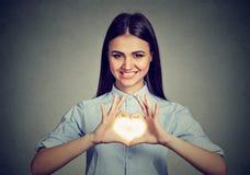 做心脏标志用手的快乐的妇女 免版税库存图片