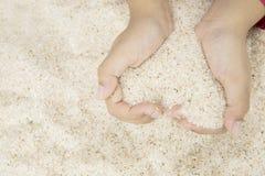 做心脏标志的孩子由海滩沙子 免版税图库摄影