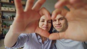 做心脏用他们的手的愉快的不同种族的夫妇慢动作画象,看照相机和微笑 浪漫 股票录像