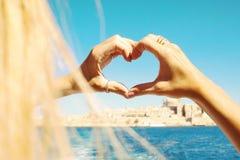 做心脏用在圆环的手的一个女孩,爱的标志从小船的在瓦莱塔,马耳他的美丽的景色 库存图片
