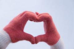 做心脏用在手套的手的女孩在雪 爱滤网符号向量 免版税库存照片
