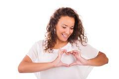 做心脏用手的美丽的少妇 免版税图库摄影