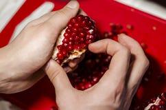 做心脏的手石榴片在红色切板 库存照片