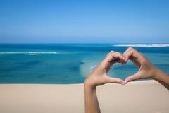 做心脏的手签字在海滩 免版税库存图片