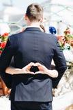 做心脏的新娘签字,当她的胳膊是在她的新郎附近时 免版税库存照片