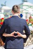 做心脏的新娘签字,当她的胳膊是在她的新郎附近时 免版税图库摄影