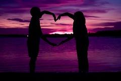 做心脏的年轻夫妇塑造与在海滩的胳膊 免版税库存照片