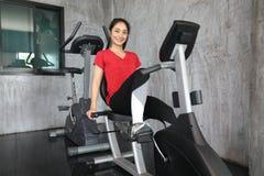 做心脏锻炼的健身房自行车的女性 库存图片