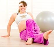 做怀孕的微笑的妇女的美好的体操 图库摄影