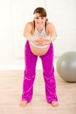 做怀孕的微笑的妇女的美好的体操 库存照片