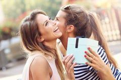 做惊奇生日礼物的两个女朋友的图片 免版税库存照片