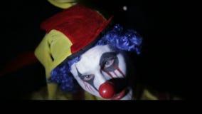 做惊恐面孔的一个鬼的疯狂的小丑的可怕射击在暗室在频率观侧器下 画象 股票视频