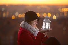 做愿望的快乐的妇女拿着一个被带领的轻的灯笼 免版税库存图片