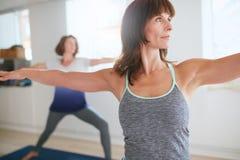 做战士姿势的健身教练员在瑜伽类 免版税库存照片