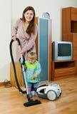 做房子清洁的妇女在客厅 免版税库存照片