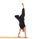 做手倒立的灵活的瑜伽人在演播室 免版税库存照片