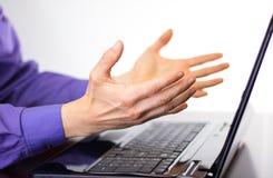 做手势`的商人在膝上型计算机显示前面的`来 免版税库存图片