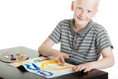 做手指画法的骄傲的年轻男孩艺术家 免版税库存照片